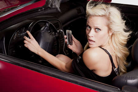 A woman with a scared expression driving and texting on her phone. photo