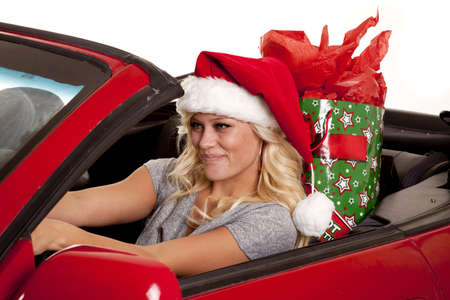 A woman sitting in her car driving down the road in her Santa hat with a present in her back seat. photo
