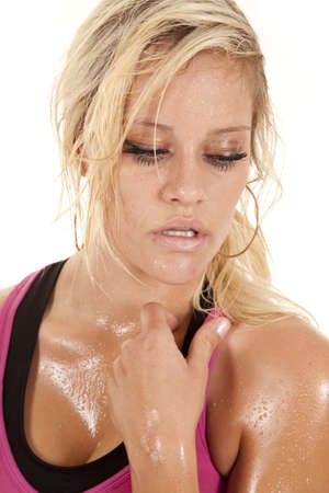 A woman is looking down and covered in sweat photo