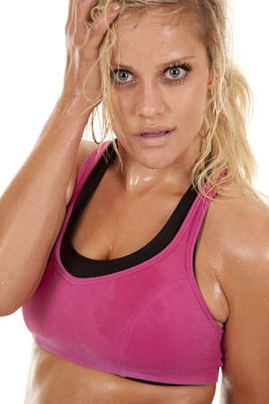 A woman with sweat on her and a pink sports bra.