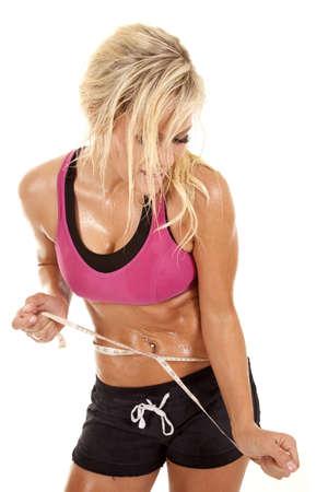 sudoroso: Una mujer cubierta de sudor tiene una cinta m�trica alrededor de su cintura.