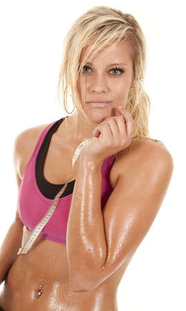 hard: A woman is standing drenched in sweat with a tape. Stock Photo