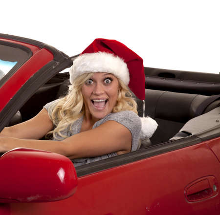 A woman with a very excited expression on her face driving while she is wearing her Santa hat. photo