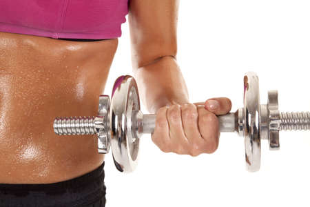 A womans body close up with weights and sweat. photo