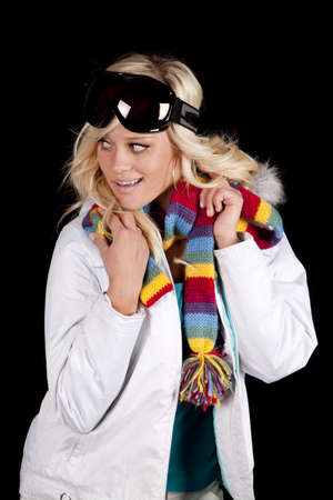 A woman is wearing a white coat with a scarf and goggles. photo