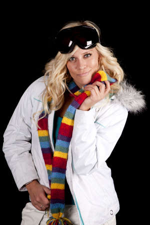 A woman is holding a colorful scarf, a winter coat, and ski goggles. photo