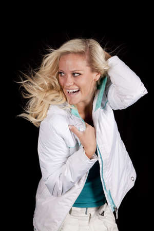 A woman is wearing a white coat in front of a black background. photo