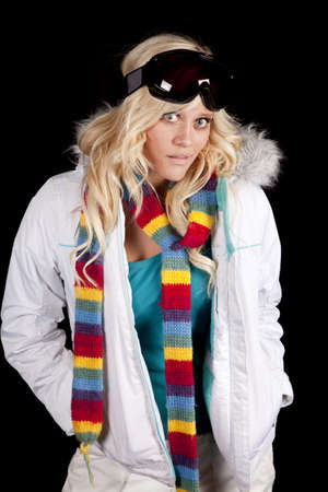 winter fashion: A woman is wearing a colorful scarf, a winter coat, and ski goggles.