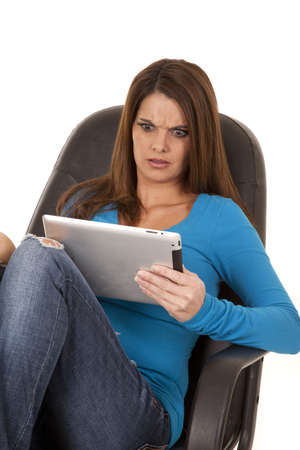 a woman looking at her tablet with a confused expression on her face. photo