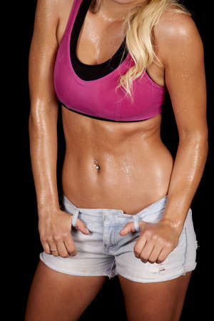sweaty: A womans body in a pink sports bra.  She is covered in sweat.