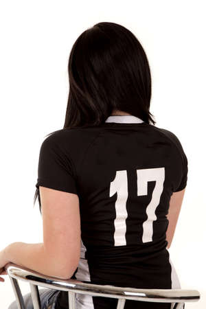 a teen girl sitting in her chair with her back to the camera while she is wearing her favorite number. photo