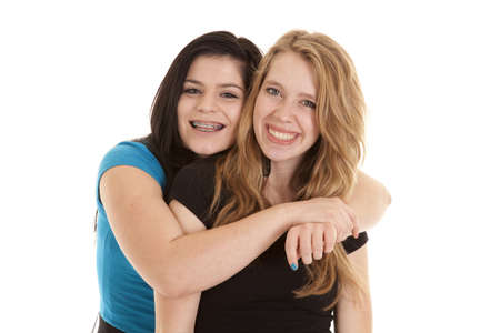 best: A teen girl hanging on to her bestfriend with a smile on their face.
