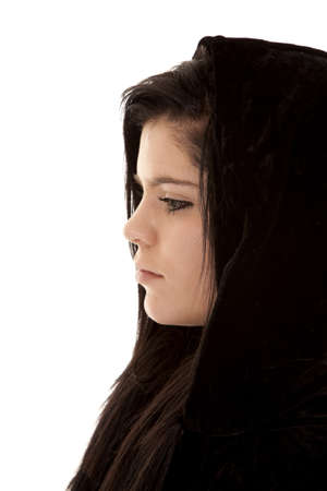 A side view of a teen girl with black hair with a sad expression on her face. photo