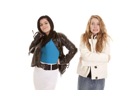 Two teenage girls in jackets one of the girls is freezing cold the other is having some fun. Stock Photo - 12092639