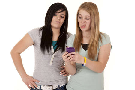 Two girls looking at a text with crazy expressions on their faces. Stock Photo - 12092530
