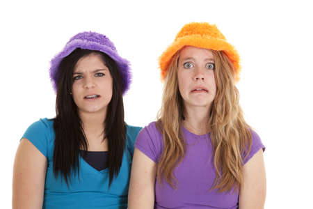 freaked out: A coulple of teens with freaked out expressions on their faces wearing fuzzy hats.