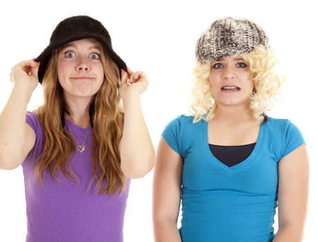 A couple of teen girls wearing funny hats and wigs with funny expressions on their faces. Stock Photo - 12092642
