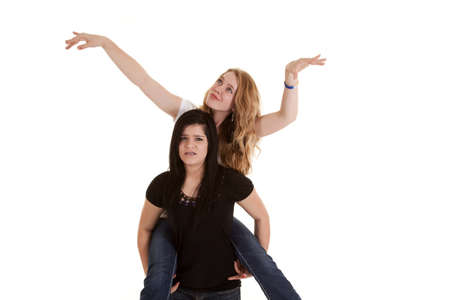 goofing: A teen holding up her friend on her back while her friend is goofing around.