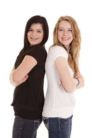 a couple of teen girls standing back to back with smiles on their faces. Stok Fotoğraf - 12092720