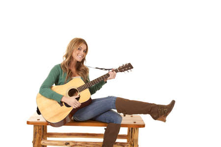 a woman sitting on a bench relaxing and playing her guitar.