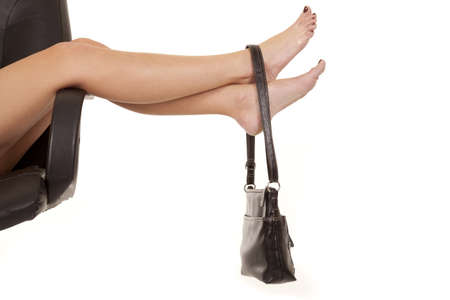 long toes: A womans legs with a purse hanging on the ankle of the woman.
