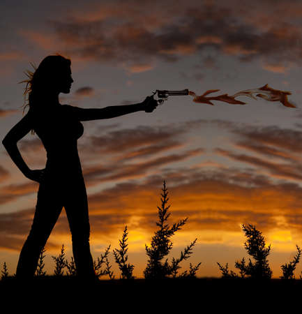 A silhouette of a woman pointing a gun with flames coming out of the end of the pistol photo