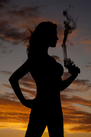 A silhouette of a woman holding up her pistol with flames coming out the end of the pistol photo