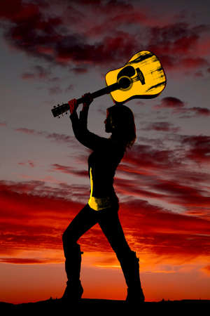 a silhouette of a woman getting ready to smash her guitar. Imagens