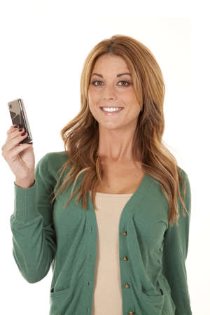 A woman with a smile on her face holding her cell phone. photo