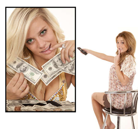 a woman watching a woman on the big screen tv holding a bunch of money. photo