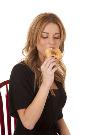 a woman taking a bite out of a glazed donut. photo