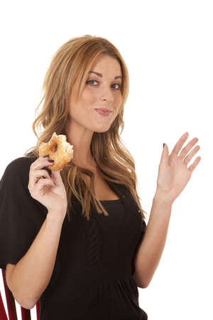 a woman enjoying every bite of her donut. photo