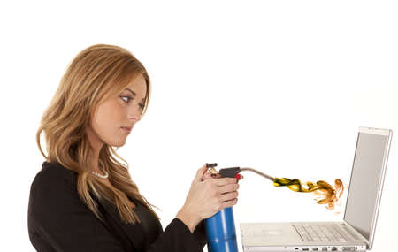 not ready: A business woman not happy with her laptop getting ready to torch it with fire.