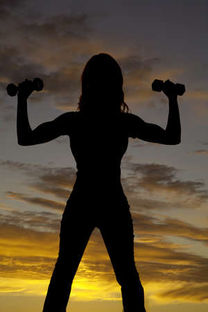 brunett: A silhouette of a  woman lifting weights with a beautiful sunset in the background.