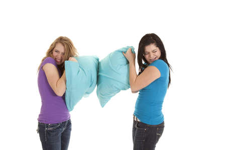 thier: Two teenage girls hiding behind thier pillows trying not to get hit. Stock Photo