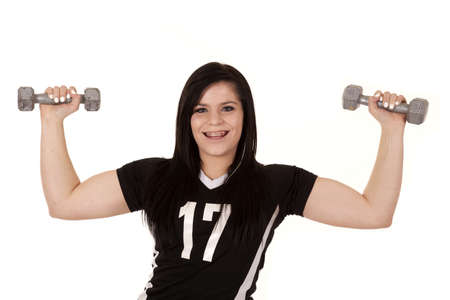 a teen girl lifting weights and showing off her muscles. photo