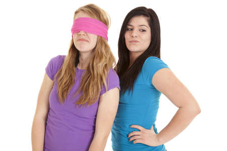 A teen girl enjoying having her friend blindfolded.