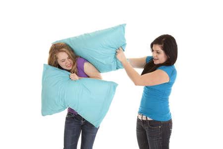 Teenage girls having a pillow fight with blue pillows. 免版税图像