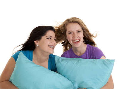 two teen girls holding on to their pillows laughing.
