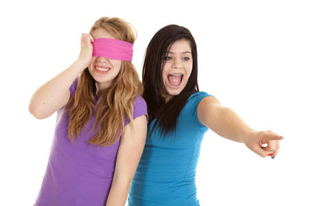 A teen girl pointing and laughing while her friend is blindfolded. 免版税图像