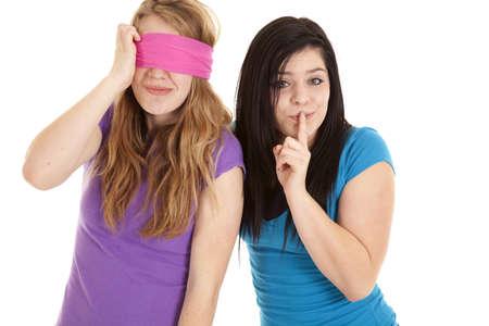 blindfold: A teen girl blindfolding her friend keeping a secret.