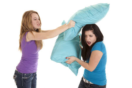 Two teens having a serious pillow fight with each other.