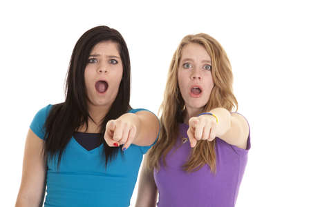 Two teen girls with shocked expressions on their faces pointing their fingers at the camera.