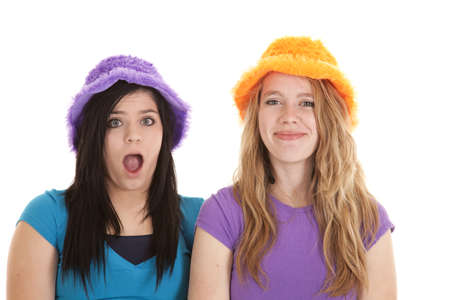 Two teen girls in silly hats one has a shocked expression on her face the other has a happy smile. photo