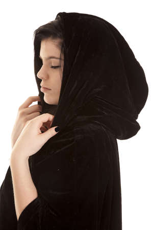 a teen wearing a black cloak with her eyes closed.