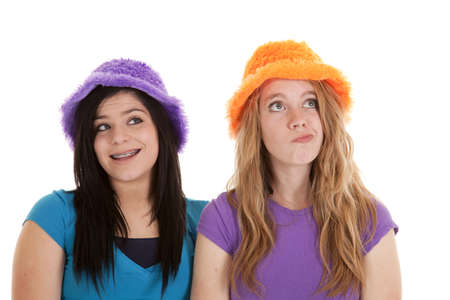 Two teens in their orange an purple fuzzy hats having some fun. photo