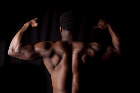 A man showing off his back muscles on a black background. photo