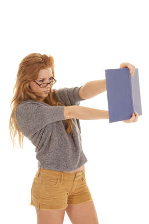 A woman holding out her book so she can see better while wearing glasses.