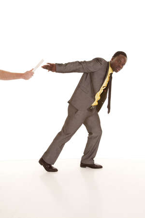 A man's arm handing off a baton to a business man who is in a suit and tie. photo