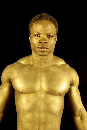 body paint: un hombre pintado de oro mostrando su cuerpo tonificado.